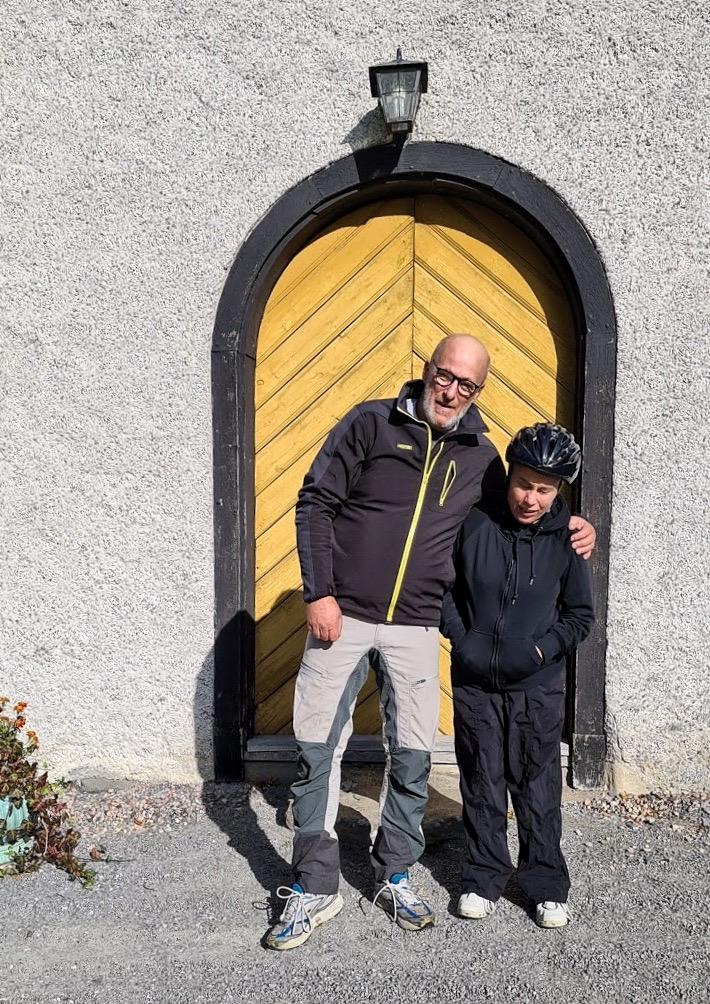 Porträttbild på 2 personer framför en stor gul träport, huset är i vit sten.